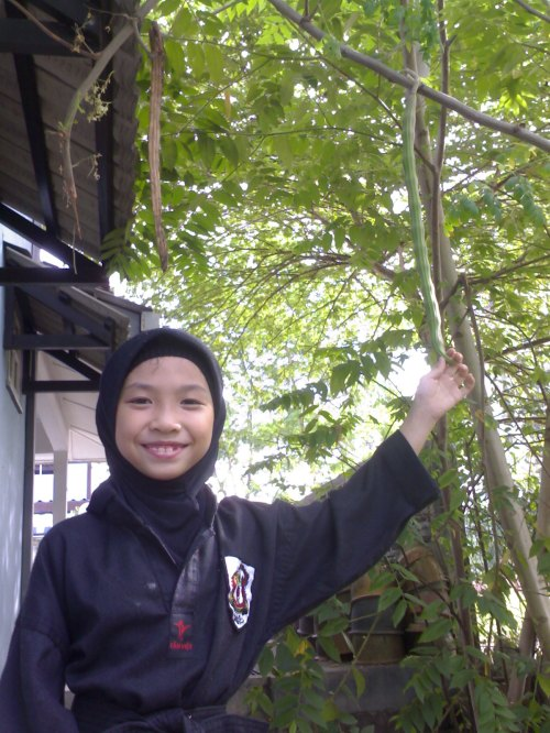 My little sister, Anisah (in her silat uniform) holding one of the many fruits.